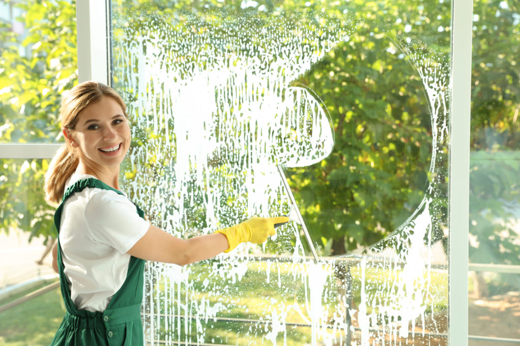 Female janitor cleaning window with squeegee indoors
