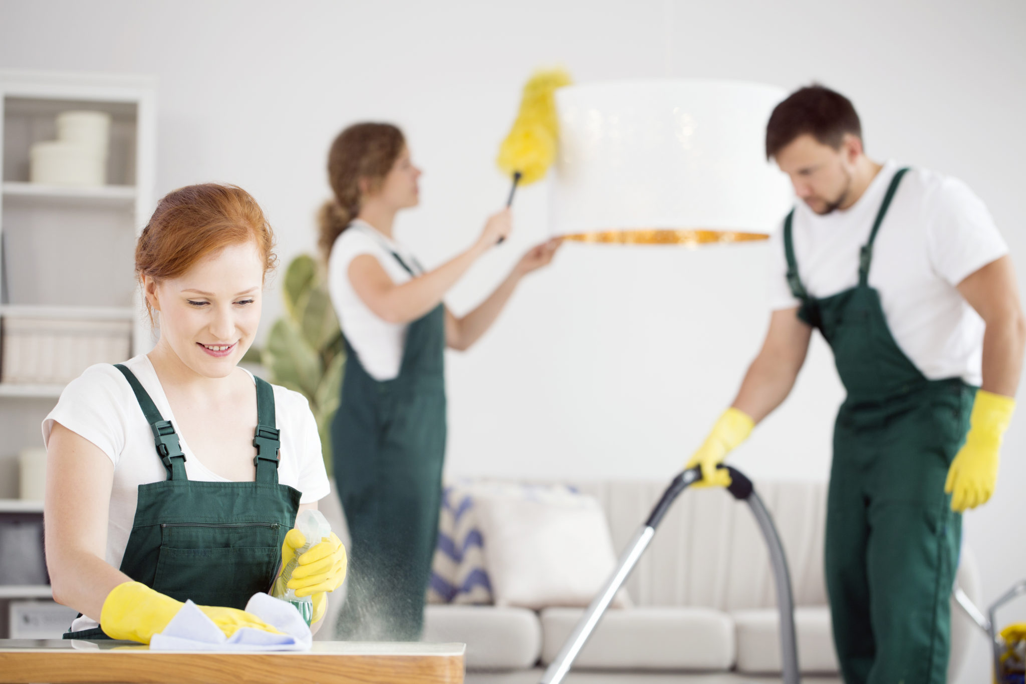 One woman dusting a table, second woman dusting a lamp and vacuuming man in green dungarees and yellow gloves