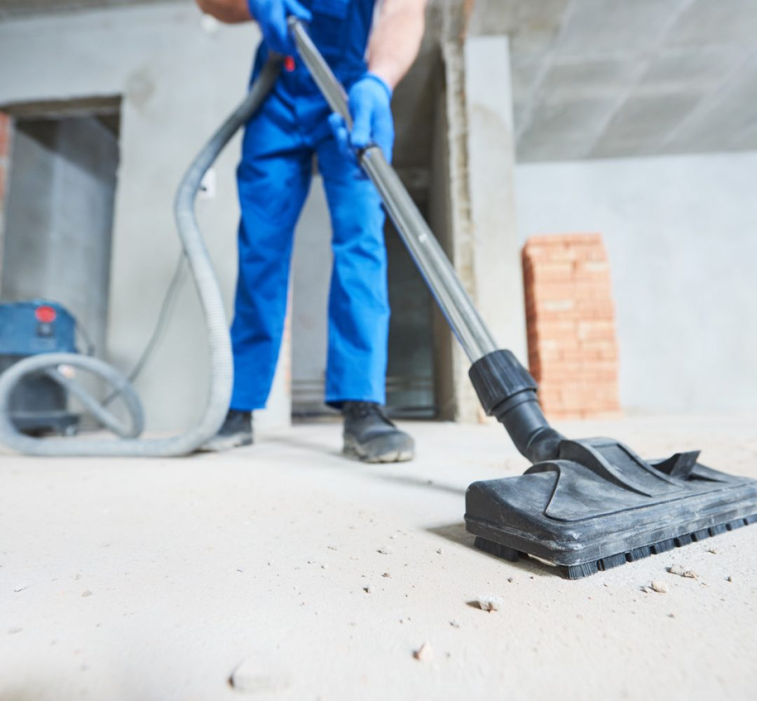 young woman cleaning and removing construction dust with vacuum cleaner after repair