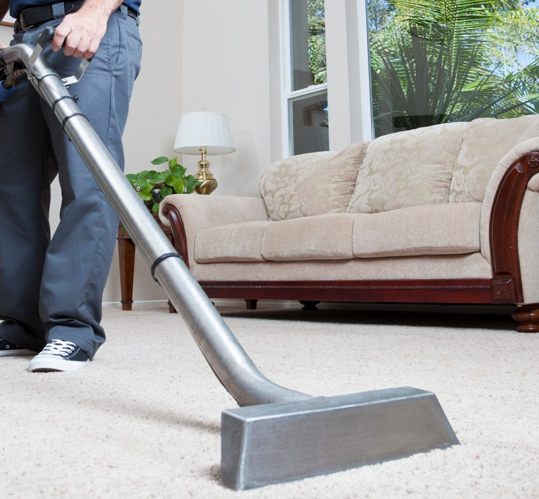 Man cleaning carpet in home